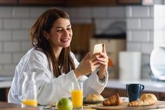 Młoda uśmiechnięta kobieta w bathrobe właśnie wstającym w ranku w kuchni używać mądrze telefon zdjęcia royalty free
