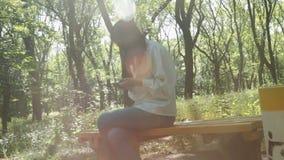 Młoda uśmiechnięta kobieta z długie włosy w lato parku siedzi na use smartphone i ławce zbiory