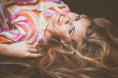 Młoda uśmiechnięta kobieta z długim blondynka włosy kłama puszka studia strzał Zdjęcia Royalty Free