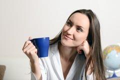 Młoda uśmiechnięta kobieta z filiżanką kawy siedzi na leżance w pokoju błękitną herbatą lub, i chce odpoczywać, mąż, nowy dom, dz fotografia stock