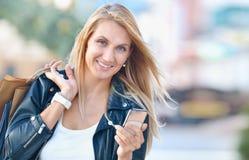 Młoda uśmiechnięta kobieta z shoping torbami trzyma komórkowego telefon Zdjęcie Royalty Free