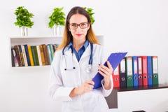 Młoda uśmiechnięta kobiety lekarka w mundurze w doktorskim ` s ofice z schowkiem obrazy royalty free
