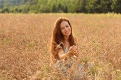 Młoda uśmiechnięta miedzianowłosa dziewczyna na pszenicznym polu joyfully egzamininuje obierań spikelets obrazy royalty free