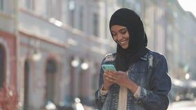 Młoda uśmiechnięta muzułmańska kobieta jest ubranym hijab chustki na głowę pozycję w centrum miasta i używa smartphone Komunikacj zdjęcie wideo