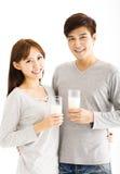 Młoda uśmiechnięta para pije mleko Fotografia Stock
