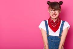 Młoda uśmiechnięta słodka dziewczyna patrzeje na boku, będący ubranym przypadkową bielu t koszula, cajgów kombinezony, czerwone b obrazy stock
