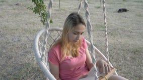 """MÅ'oda uczennica czytajÄ…ca książkÄ™ o huÅ›tawce w parku o zachodzie sÅ'oÅ""""ca. Prostuje wÅ'osy i huÅ›tawki na biaÅ'ym zdjęcie wideo"""