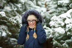 Młoda urocza blond kobieta jest ubranym błękit w szkłach okapturzał żakiet ma zabawę w śnieżnym zima lesie outdoors Natura sezonu Zdjęcie Royalty Free