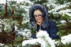 Młoda urocza blond kobieta jest ubranym błękit w szkłach okapturzał żakiet ma zabawę w śnieżnym zima lesie outdoors Natura sezonu Obrazy Stock