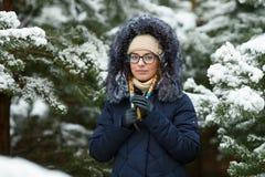 Młoda urocza blond kobieta jest ubranym błękit w szkłach okapturzał żakiet ma zabawę w śnieżnym zima lesie outdoors Natura sezonu Zdjęcia Royalty Free