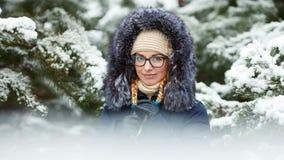 Młoda urocza blond kobieta jest ubranym błękit w szkłach okapturzał żakiet ma zabawę w śnieżnym zima lesie outdoors Natura sezonu Obrazy Royalty Free