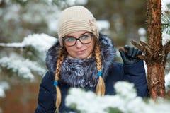 Młoda urocza blond kobieta jest ubranym błękit w szkłach okapturzał żakiet ma zabawę w śnieżnym zima lesie outdoors Natura sezonu Fotografia Royalty Free