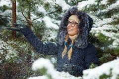 Młoda urocza blond kobieta jest ubranym błękit w szkłach okapturzał żakiet ma zabawę w śnieżnym zima lesie outdoors Natura sezonu Fotografia Stock