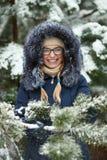Młoda urocza blond kobieta jest ubranym błękit w szkłach okapturzał żakiet ma zabawę w śnieżnym zima lesie outdoors Natura sezonu Obraz Royalty Free