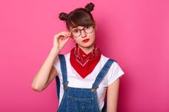 Młoda urocza kobieta dotyka eyewear z jest ubranym drelichowych kombinezony, przypadkową bielu t koszula, czerwone bandany na szy obrazy royalty free