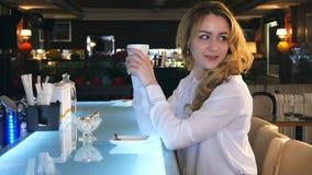 Młoda wspaniała kobieta pije kawę i zamyślenie patrzeje z sklep z kawą okno podczas gdy cieszący się jej czas wolnego Obrazy Royalty Free
