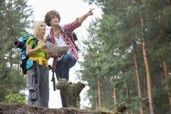 Młoda wycieczkuje para dyskutuje nad kierunkiem w lesie z mapą obraz royalty free