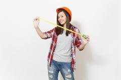 Młoda zabawy kobieta w przypadkowych ubraniach, ochronnej budowy hełma mienia zabawki taśmy odizolowywającej na bielu pomarańczow obraz stock