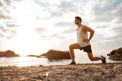 Młoda zdrowa mężczyzna atleta robi kucnięciom przy plażą Obrazy Stock