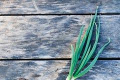 Młoda zielona cebula na starej drewnianej powierzchni, tło fotografia stock