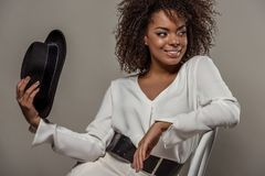 Młoda zmysłowa amerykanin afrykańskiego pochodzenia kobieta w białym koszulowym mienia fedora kapeluszu fotografia stock