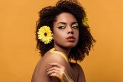 Młoda zmysłowa amerykanin afrykańskiego pochodzenia kobieta z artystycznym makijażem i gerbera w włosiany patrzeć strona obraz royalty free