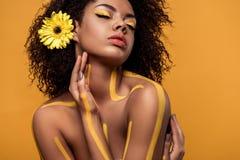 Młoda zmysłowa amerykanin afrykańskiego pochodzenia kobieta z artystycznym makijażem i gerbera w włosy fotografia stock