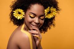 Młoda zmysłowa amerykanin afrykańskiego pochodzenia kobieta z artystycznym makijażem i gerberas w włosy zdjęcie royalty free