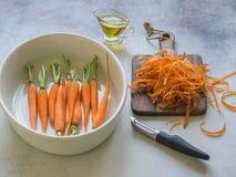 Młode świeże obrane pomarańczowe marchewki w białej owalnej ceramicznej niecce, gotowa piec i marchewka czyścili na drewnianej de zdjęcia royalty free