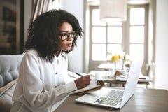 Młode amerykanin afrykańskiego pochodzenia dziewczyny writing notatki w restauracyjnym portrecie dama patrzeje w laptopie z w szk Obraz Stock