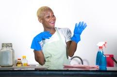 Młode atrakcyjnego i szczęśliwego czarny afrykanin kobiety cleaning domu amerykańskiego kuchennego kładzenia błękitne płuczkowe g Fotografia Royalty Free
