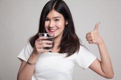 Młode Azjatyckie kobiet aprobaty z szkłem woda pitna Obrazy Stock