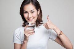 Młode Azjatyckie kobiet aprobaty z szkłem woda pitna Zdjęcia Stock