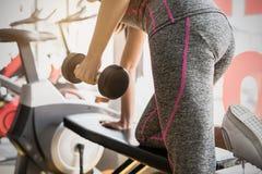 Młode azjatykcie kobiety podnosi dumbbell w sporta gym fotografia royalty free