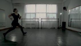 Młode baleriny ubierali w czarnych leotards robią baletniczego ruchu w białej taniec klasie jeden po drugim Baleriny robią zbiory wideo