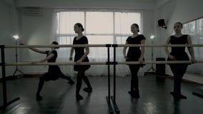 Młode baleriny ubierali w czarnych leotards robią baletniczego ruchu jeden po drugim blisko baletniczego barre Baleriny robią zbiory