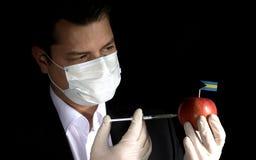 Młode biznesmena wstrzykiwania substancje chemiczne w jabłko z Bahamia obraz stock