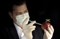 Młode biznesmena wstrzykiwania substancje chemiczne w jabłko z Jamajka zaznaczają obrazy royalty free