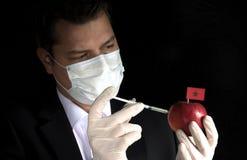 Młode biznesmena wstrzykiwania substancje chemiczne w jabłko z marokańczykiem zaznaczają na czarnym tle zdjęcie stock