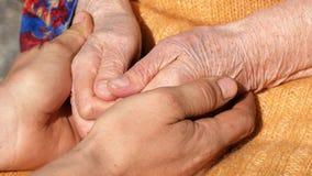Młode brudne pracujące męskie ręki pociesza starszą parę ręki babci plenerowy zakończenie up Fotografia Royalty Free