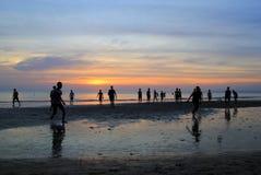 Młode chłopiec bawić się futbol na plaży na tle kolorowy zmierzch Fotografia Royalty Free