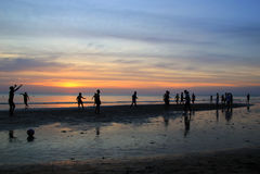 Młode chłopiec bawić się futbol na plaży na tle kolorowy zmierzch Obrazy Royalty Free