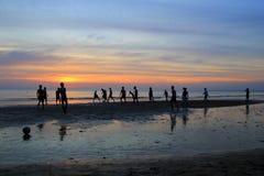 Młode chłopiec bawić się futbol na plaży na tle kolorowy zmierzch Zdjęcie Stock