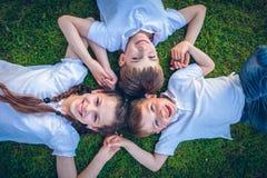 Młode chłopiec i dziewczyny kłama na zielonej trawie Obraz Stock