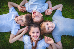 Młode chłopiec i dziewczyny kłama na zielonej trawie Zdjęcia Stock