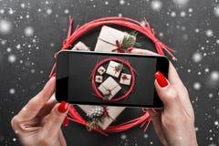 Młode damy które strzelają Bożenarodzeniowego tło z ich telefonem Handmade prezenty w czerwonym okręgu Skutek płatki śniegu fotografia stock
