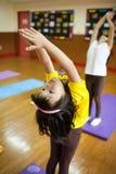 Młode dzieci biorą joga klasę z ich nauczycielem Zdjęcia Stock