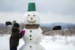 Młode dziecko chłopiec koniec robi uśmiechniętego bałwanu w wiadro kapeluszu, szalik i rękawiczki na pustym zimy polu, kształtuje zdjęcie royalty free