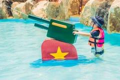 Młode dziecko ma zabawę z armatką wodną w aqua parku zdjęcia royalty free