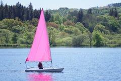 Młode dziecko uczenie żeglować na różowym jachcie na jeziorze dla odtwarzania fotografia royalty free